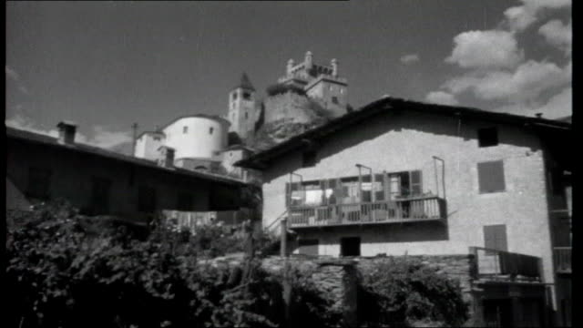 vidéos et rushes de gateway to italy general view down valley castle of saint pierre with its own church next to it on the same rock village with mountains in background... - rock face