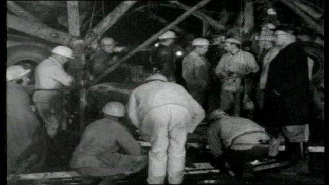 german mine disaster; germany: lengede: ext b/w mine buildings with pit wheel and flag at half mast reporter to camera night various of rescuers... - full stock videos & royalty-free footage
