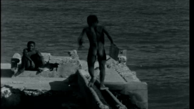vídeos de stock, filmes e b-roll de ghana 2 waves washing onto shoreline with low cliffs and buildings on top palm trees against the sky tilt down to lots of small basic boats pulled up... - nu