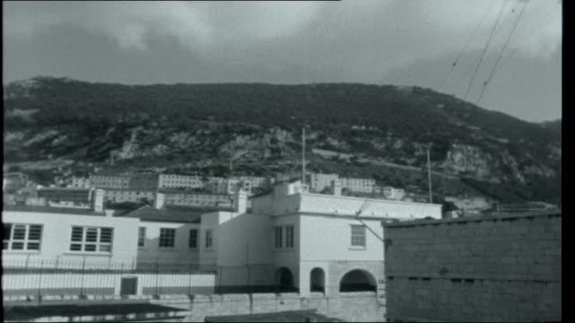 gibraltar 1962 buildings of gibraltar arches over road - gibraltar bildbanksvideor och videomaterial från bakom kulisserna