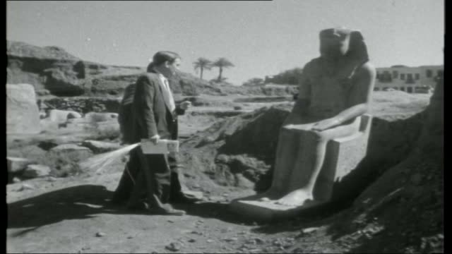 grandeur of egypt; man along on donkey loaded with hay / shots of colossi of memnon / reporter climbing colossi statues / settlement on hillside... - 1950 1959 stock videos & royalty-free footage