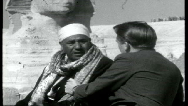 grandeur of egypt; various shots of street scenes, people and traffic along, camels along giza: the sphinx and the pyramids / reporter seated on... - 1950 1959 stock videos & royalty-free footage