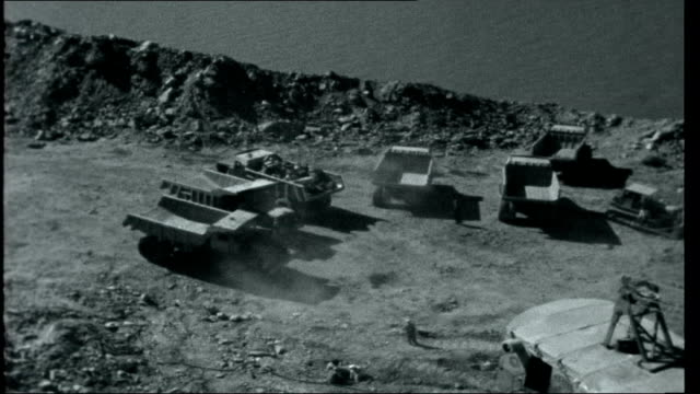 High Dam over Abu Simbel 1959 Rocks on east bank of River Nile Russian excavator machine removing earth and earth removal trucks at site lorries...