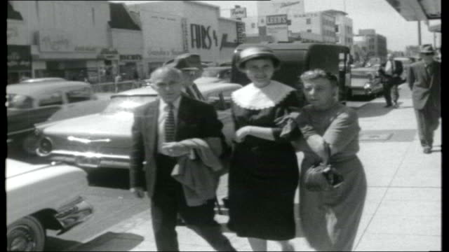 hollywood today; traffic along / reporter and cameraman along through empty film set / people along boulevard / police officer along / man smoking... - boulevard video stock e b–roll