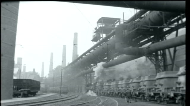 vidéos et rushes de how many germanies; ext crane unloading rocks from barge at dockside / general view of coal mine with piles of coal and steam train pulling coal... - 1950 1959