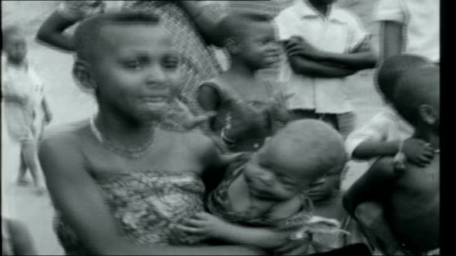Hunger in the Congo CONGO EXT Hands playing bongo Baluba villagers gathered round men sitting on ground playing a large musical instrument and bongos...