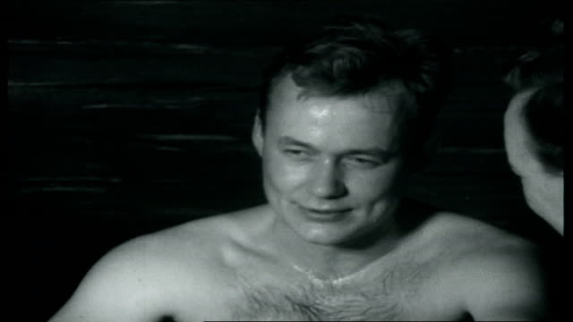 vídeos de stock e filmes b-roll de land of two christmases int naked man having back beaten with birch twigs naked tyrrell sitting in sauna with other naked men as describing the dry... - sauna