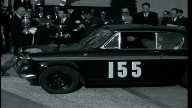 vídeos y material grabado en eventos de stock de monte carlo rally 1962 women applauding pat moss collecting trophy from princess grace photographers and onlookers unidentified drivers departing car... - monte rainier