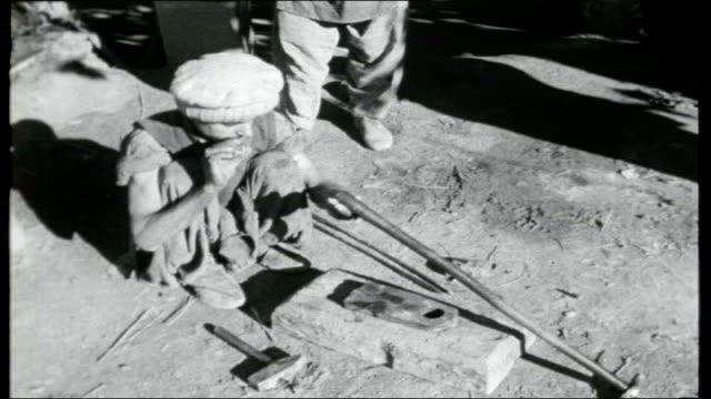 vídeos y material grabado en eventos de stock de north west frontier pakistan ext mountainous countryside / sign ' darra tribal arms factories go slow' / tribal factory manufacturing rifles / guns... - cross legged