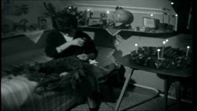 stockvideo's en b-roll-footage met pestalozzi christmas; fir cones attached to wreath with cotton thread / woman looking down / thread wound round wreath / woman working making... - krans