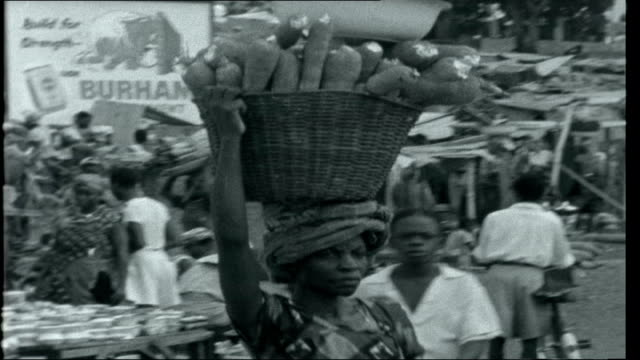vidéos et rushes de portrait of a northerner ext hills and town in distance below crowded streets streethawkers selling items and people mostly igbo women walking around... - igname