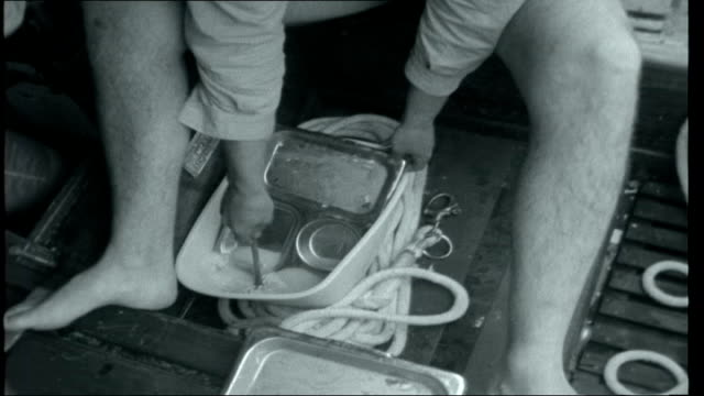 sellers at home / tall ships race crew member wringing out wet sock into wellington boot then putting it back on crew member making cup of tea in... - galeere stock-videos und b-roll-filmmaterial