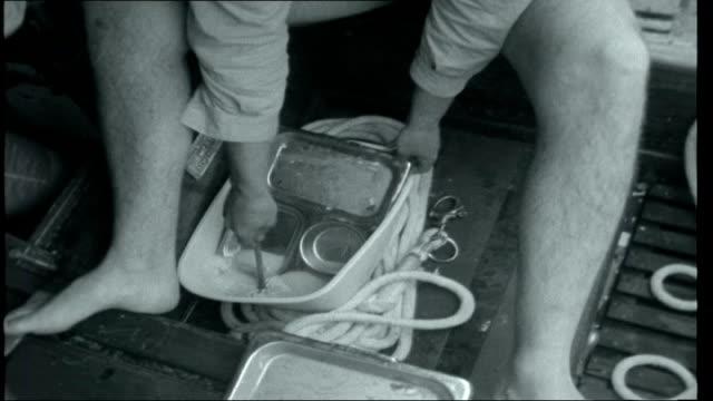 sellers at home / tall ships race crew member wringing out wet sock into wellington boot then putting it back on crew member making cup of tea in... - kapten bildbanksvideor och videomaterial från bakom kulisserna