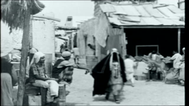 Sheikh Shakhbut's Oil Shanty town village of Abu Dhabi includes makeshift housing and washing hanging on lines/ Woman washing clothes on beach/...