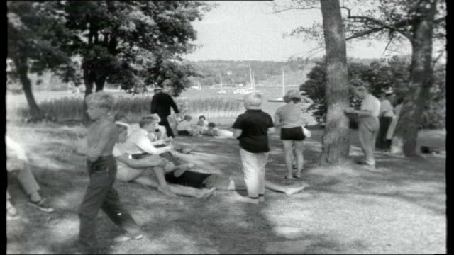 stockvideo's en b-roll-footage met summer in stockholm day people sunbathing on beach near stockholm / women along on beach / people in shady wooded area near beach / various of... - aangelegd