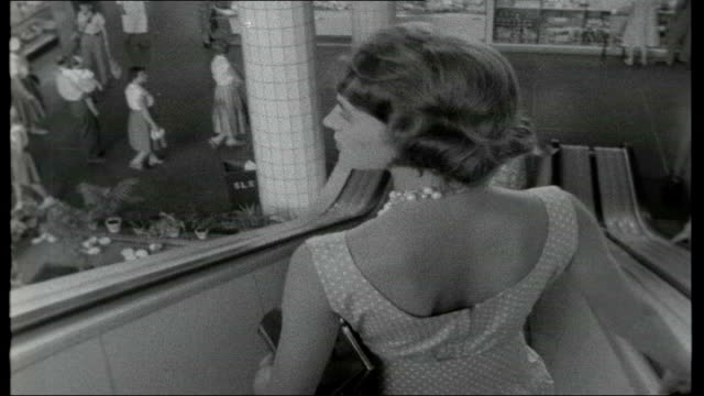summer in stockholm; int reporter going down escalator to underground supermarket / various of people in indoor market / woman being served at cheese... - 1950 1959 bildbanksvideor och videomaterial från bakom kulisserna