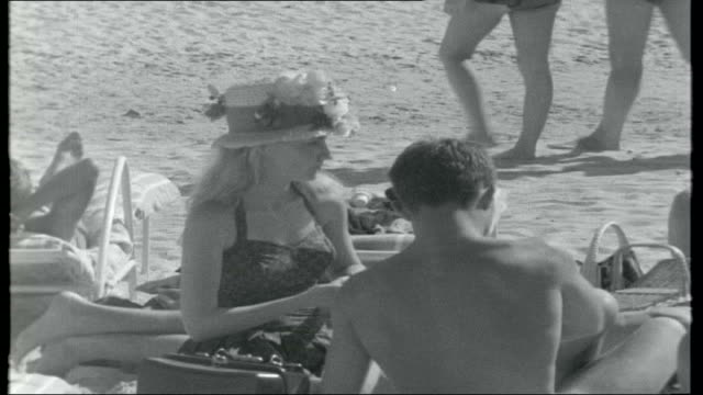stockvideo's en b-roll-footage met the world of st tropez gv bar / restaurant at nearby tahiti beach young people sitting at table at beach restaurant reporter along past sunbathers... - tahiti