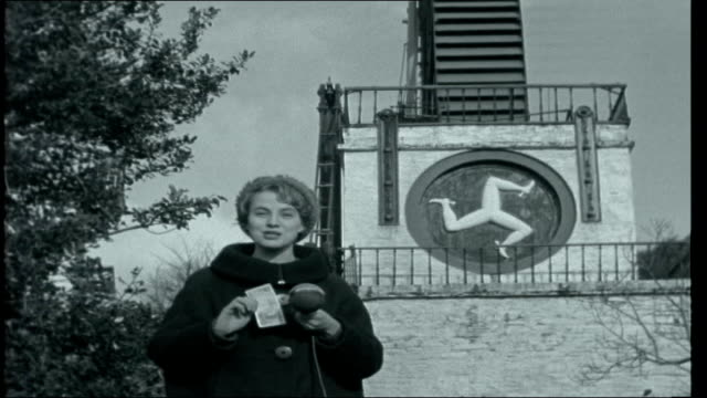 two islands laxey reporter to camera with isle of man logo of three running legs on plinth to waterwheel behind her and quote their motto 'wherever... - sockel stock-videos und b-roll-filmmaterial