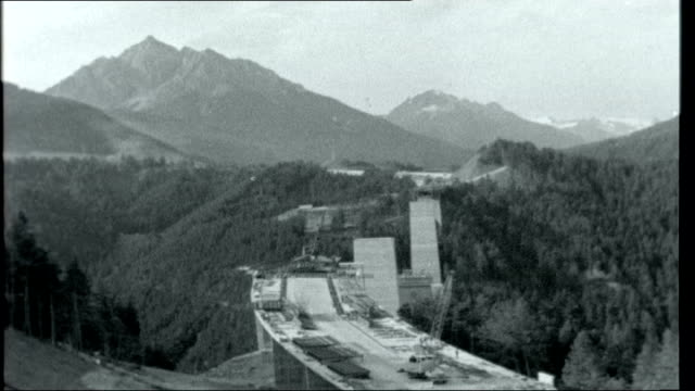 wheels through the alps ext part of bridge under construction tilt up to pillars of unfinished sections and mountains in background two men working... - brenner pass stock videos and b-roll footage