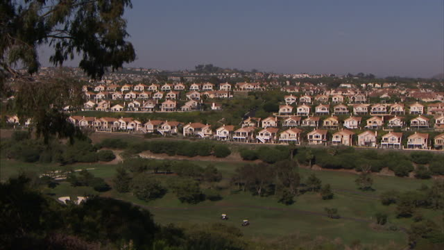 row after row of suburban homes flank a golf course. - golf cart stock videos and b-roll footage