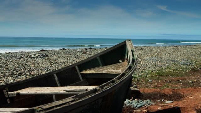 row boat on stony beach - penisola di bassa california video stock e b–roll