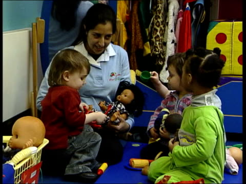 chief medical officer criticises wakefield report itv england london children in playgroup playing with dolls young child holding doll side cms... - itv late news stock-videos und b-roll-filmmaterial