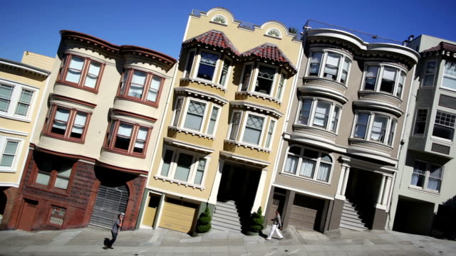 row houses appear to slant as pedestrians walk along a street in san francisco. - victorian stock videos & royalty-free footage