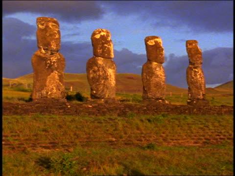 row of 4 stone statues in warm sunlight on terraced field / easter island - einige gegenstände mittelgroße ansammlung stock-videos und b-roll-filmmaterial