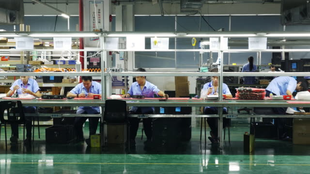 A row of 5 Chinese workers assemble circuit boards on an electronics production line in a large private factory