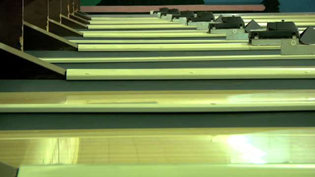 stockvideo's en b-roll-footage met row of active bowling lanes inside unidentifiable bowling alley multiple colorful bowling balls moving across slick surface of lanes horizontal lines... - bowlingbal