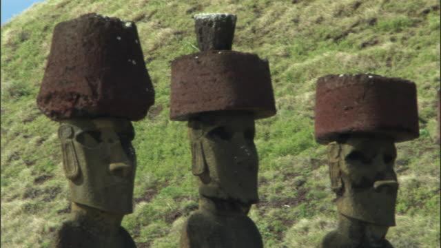 CU PAN Row of Ahu Nau Nau statues on green hill / Anakena beach, Easter Island, Chile