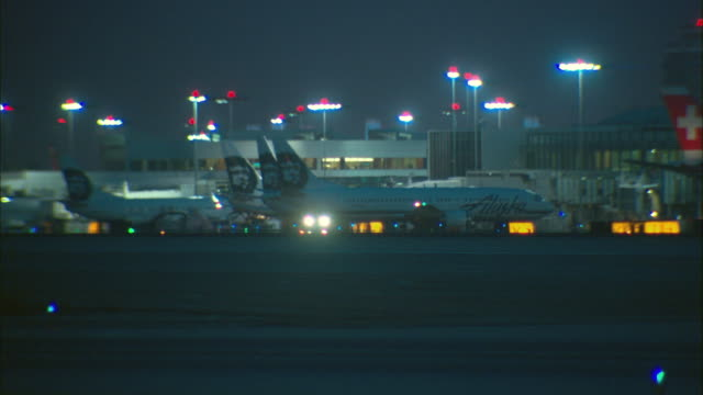 stockvideo's en b-roll-footage met ws, row of airplanes parked at terminal at night, los angeles international airport, los angeles, california, usa - lax airport
