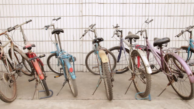 ms zo row of bicycles parked against wall / shenzhen, guangdong, china - medium group of objects stock videos & royalty-free footage