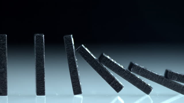 slo mo ts row of black domino tiles falling down - continuity stock videos & royalty-free footage