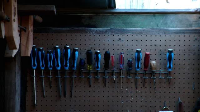 cu row of blue screwdrivers hanging from rack on wall in workshop, live oak, florida, usa - einige gegenstände mittelgroße ansammlung stock-videos und b-roll-filmmaterial