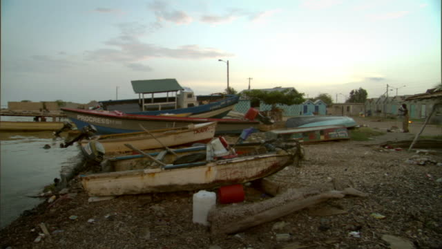 WS row of boats sitting on shore under overcast sky/ Kingston, Jamaica