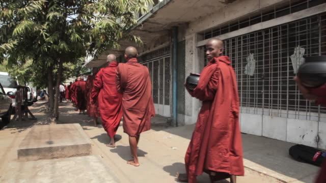 A row of Buddhist monks walk along a street in Yangon.