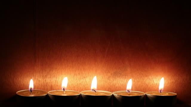 Reihe von Kerzen mit Holzwänden in dunklen Raum.