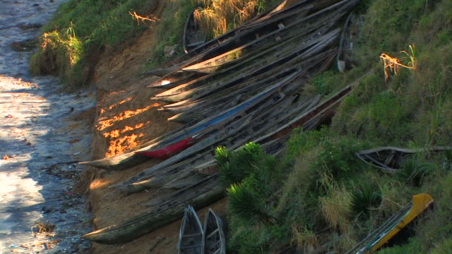 ms, row of canoes pulled up on hillside above beach, taolanaro, toliara province, madagascar - medium group of objects stock videos & royalty-free footage