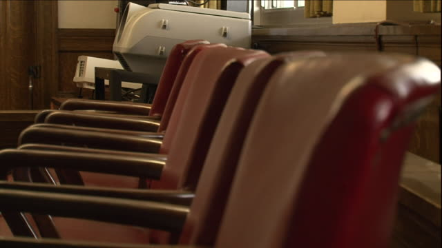 a row of chairs wait in an empty courtroom. - court room stock videos & royalty-free footage