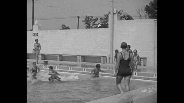 row of children standing on edge of pool gertrude ederle standing on edge of pool at right angle to them ederle tells them to jump in and they jump... - gertrude ederle stock videos & royalty-free footage