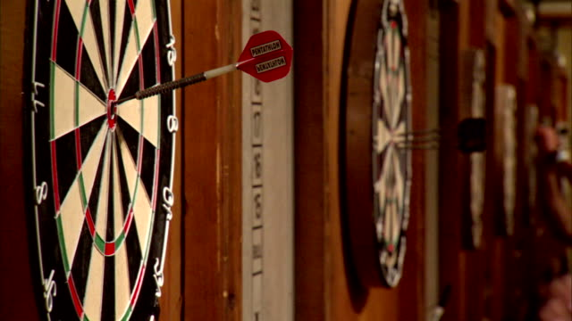 row of circular dartboards on wall, steel tip darts flying toward targets, sticking into boards, unidentifiable male hands pulling darts out of... - ダーツバー点の映像素材/bロール
