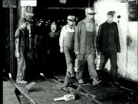 vídeos de stock e filmes b-roll de 1927 b/w ws row of coal miners walking past following miner carrying safety lamps/ pennsylvania, usa - mineiro trabalhador manual