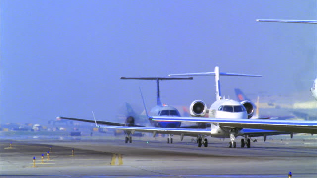 vidéos et rushes de cu, t/l, row of commercial aircrafts turning from airstrip, los angeles, california, usa - macadam