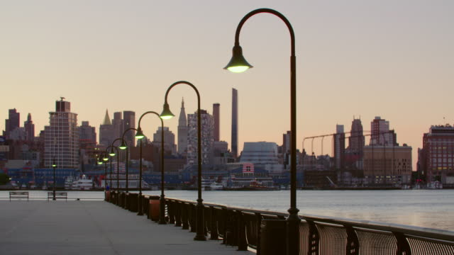 row of curved outdoor light fixtures near waterfront along hudson river. new york skyline visible in background. - ウォーターフロント点の映像素材/bロール