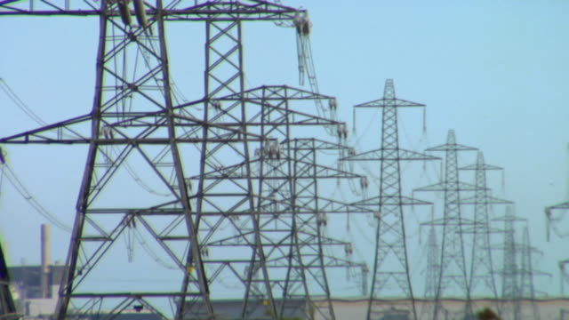 ms pan row of electricity pylons on field, dungeness, kent, united kingdom - hochspannungsmast stock-videos und b-roll-filmmaterial