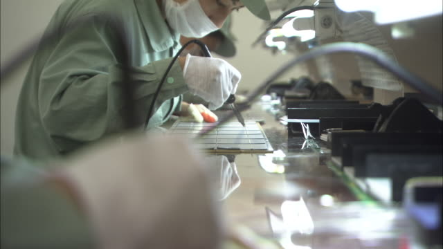 ms selective focus row of employees working on cells for solar photovoltaic panels at suntech power holdings factory, wuxi, jiangsu, china - computer chip stock videos & royalty-free footage