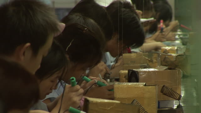 ms row of factory workers soldering electronics/ shenzhen, china - manufacturing occupation video stock e b–roll