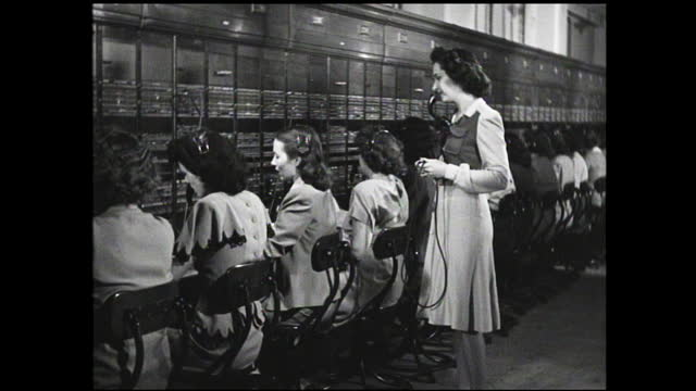 row of female operators with headsets working in front of switchboard while supervisor walks behind them - 1940 1949 stock-videos und b-roll-filmmaterial