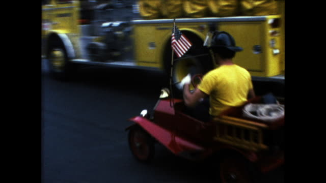 row of fire trucks driving down the street man in yellow shirt driving a small fire truck also drives on the street - 道路名の標識点の映像素材/bロール